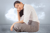 Composite image of businesswoman sitting cross legged leaning on
