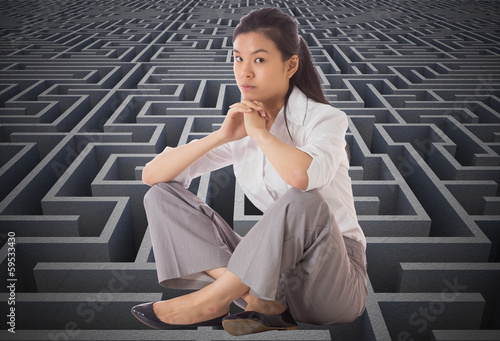 Composite image of businesswoman sitting cross legged with hands
