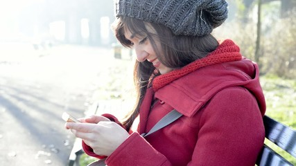 woman using cellphone tipying message sitting on a bench in the