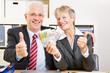 Senioren mit Euro-Scheinen halten Daumen hoch