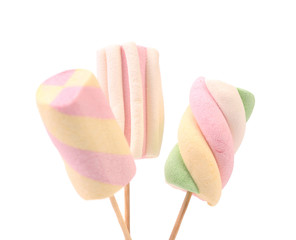 Three different marshmallow on sticks.