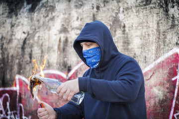 Man with burning Molotov cocktail on the wall background