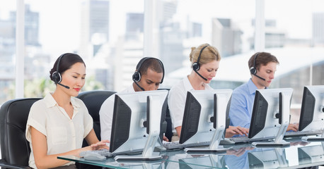 Colleagues with headsets using computers at desk