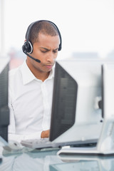 Executive with headset using computer at desk