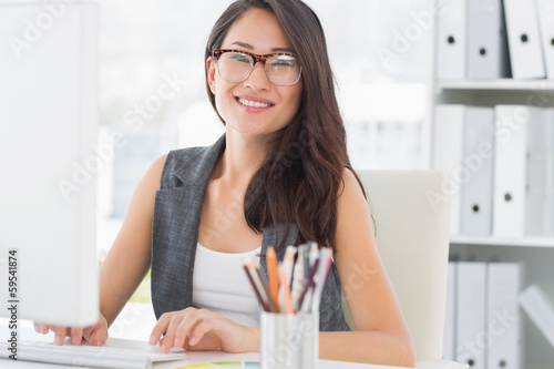 Portrait of a smiling young woman using computer