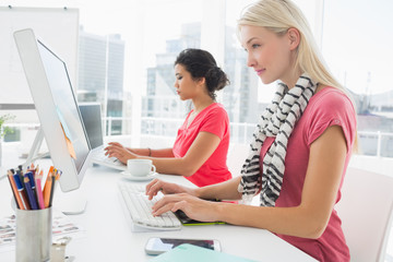Casual young women using computers in office