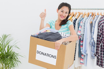 Woman with clothes donation gesturing thumbs up