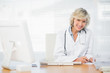 Smiling female doctor with computer at medical office