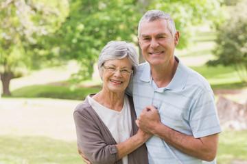 Loving happy senior couple holding hands at park