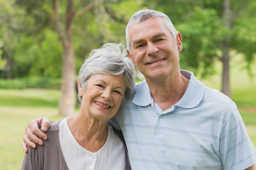 Portrait of a senior couple with arms around at park