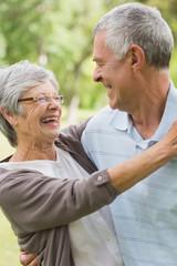 Happy senior woman embracing man at park