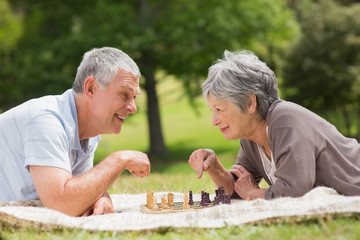Happy senior couple playing chess at park
