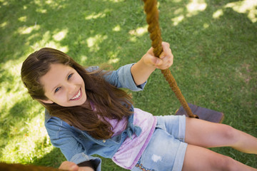 Cute little young girl sitting on swing