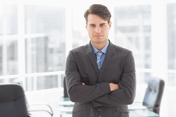 Handsome businessman leaning on board room table