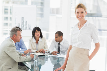 Happy businesswoman looking at camera while staff discuss behind