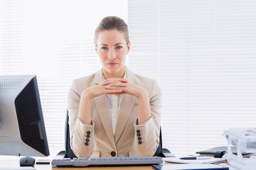 Serious businesswoman with computer at office desk