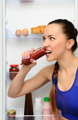 Girl eats sausage near the refrigerator