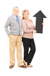 Smiling mature couple holding a big black arrow pointing up