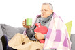 Ill middle aged man on a sofa covered with blanket drinking tea