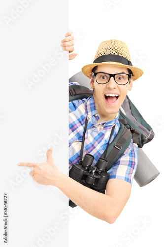 Smiling male tourist pointing on a blank panel