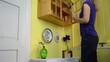 girl takes jars of pickled vegetables align them on the shelves