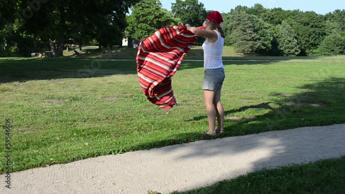 Woman girl with headscarf on head shake rug and flex it in park