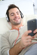 Young man relaxing in sofa with headphones on