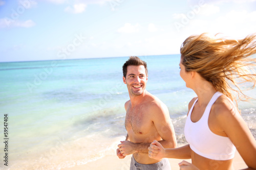 Cheerful couple training on the beach