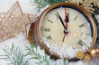 Clock with fir branches and Christmas decorations under snow