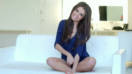 Smiling Beauty Flirting While Sitting on White Sofa