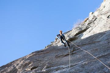 A rock climber abseiling off a climb