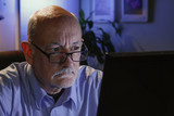 Close up of serious older man reading off his computer
