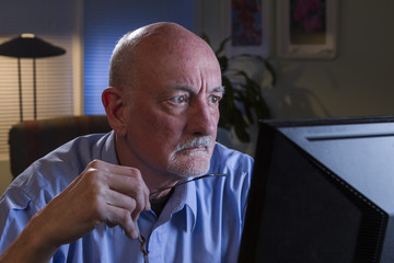 Older man looks serious as he reads computer monitor, horizontal