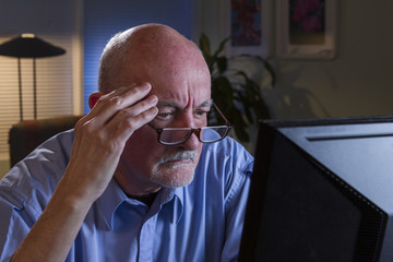 Man looks worried as he reads computer monitor, horizontal