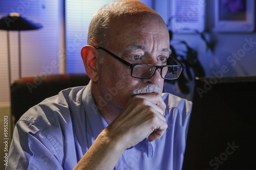 Older man using his home computer, horizontal