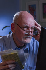 Stressed older man paying bills online, vertical