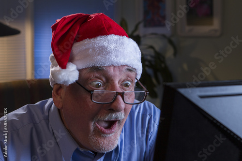 Older man in Santa hat with shocked reaction, horiziontal