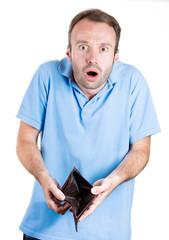 Shocked, broke man holding empty wallet,