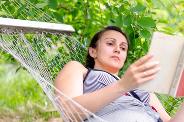 Woman reading whilst relaxing in a hammock