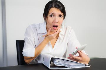 Geschäftsfrau blickt schockiert nach der Berechnung