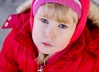 Cute blonde little girl in a red jacket