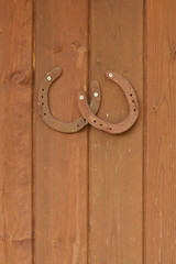 Old rusty and worn horseshoes on a wooden door
