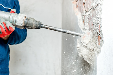 man using a jackhammer to drill into wall. professional worker