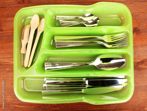 Green plastic cutlery tray with checked cutlery and wooden