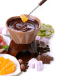 Chocolate fondue with marshmallow candies and fruits, isolated
