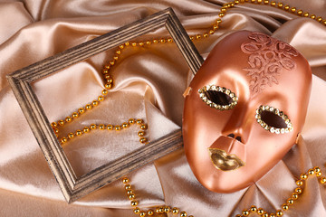 Mask on golden fabric background