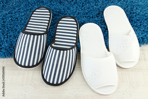 Striped and white slippers on floor background