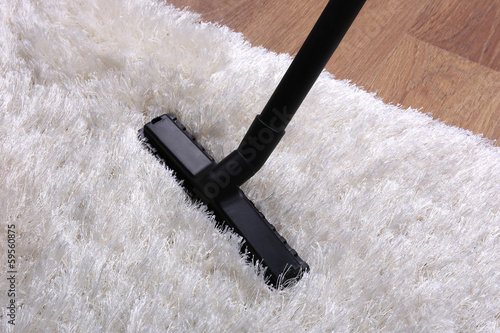 Vacuuming carpet in house