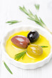 three kinds of olives and rosemary in a bowl with olive oil