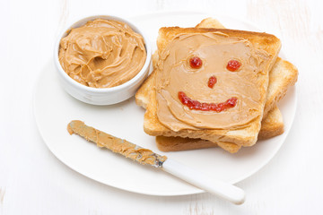 toast with peanut butter and a painted smile, top view